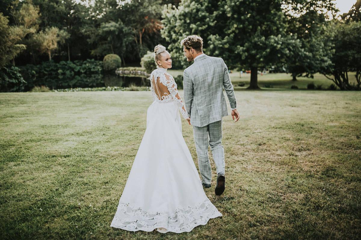 Grijs groen trouwpak in park met bruid
