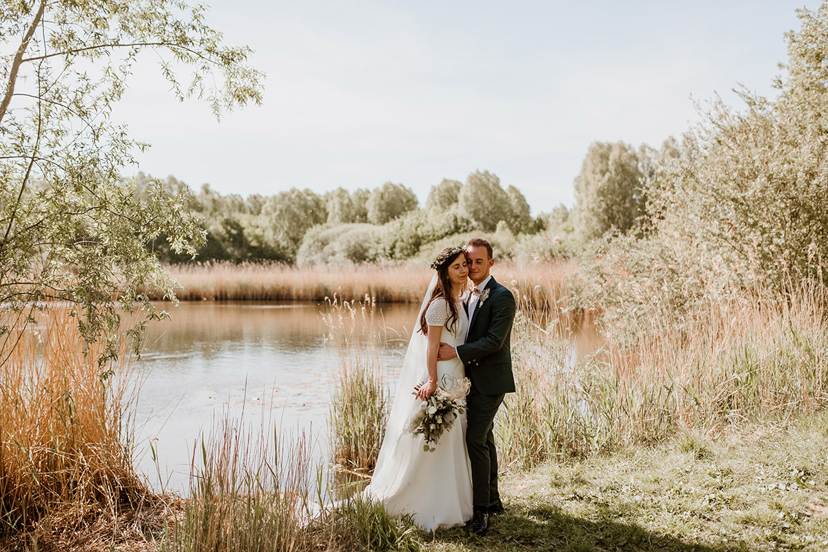 Poseren bruid en bruidegom bij meer