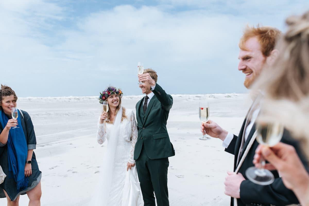 Bruidspersoneel proost met bruidspaar. Zandbanken. Mosgroen trouwpak op maat, Wild at heart bruidsjurk