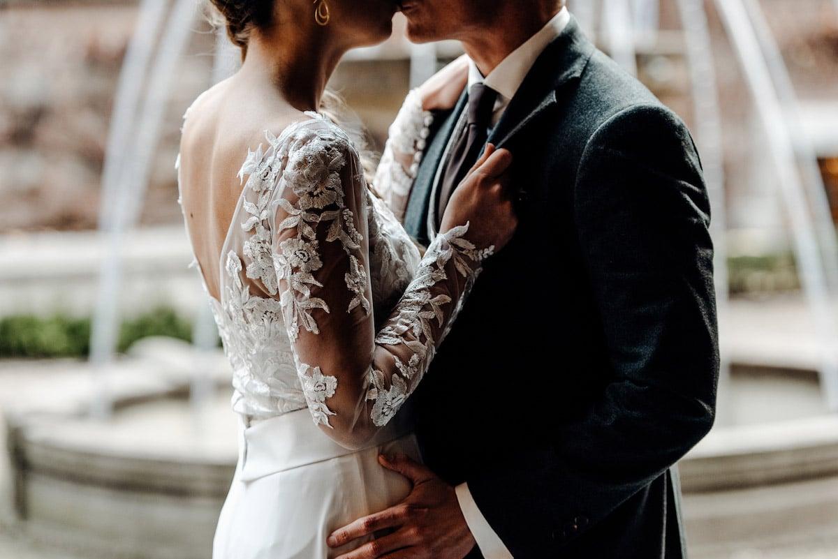 Kusmoment bruidspaar in groen trouwpak