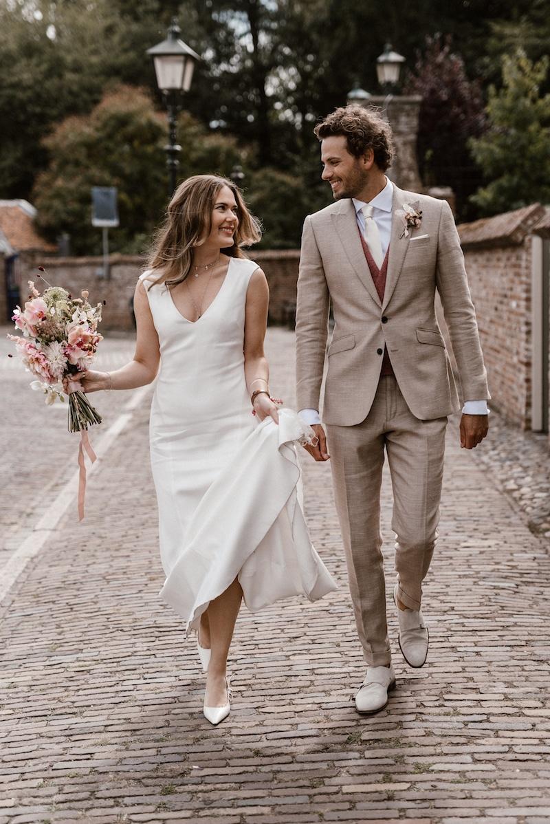 Beige trouwen, rode details, corsage bloemstuk