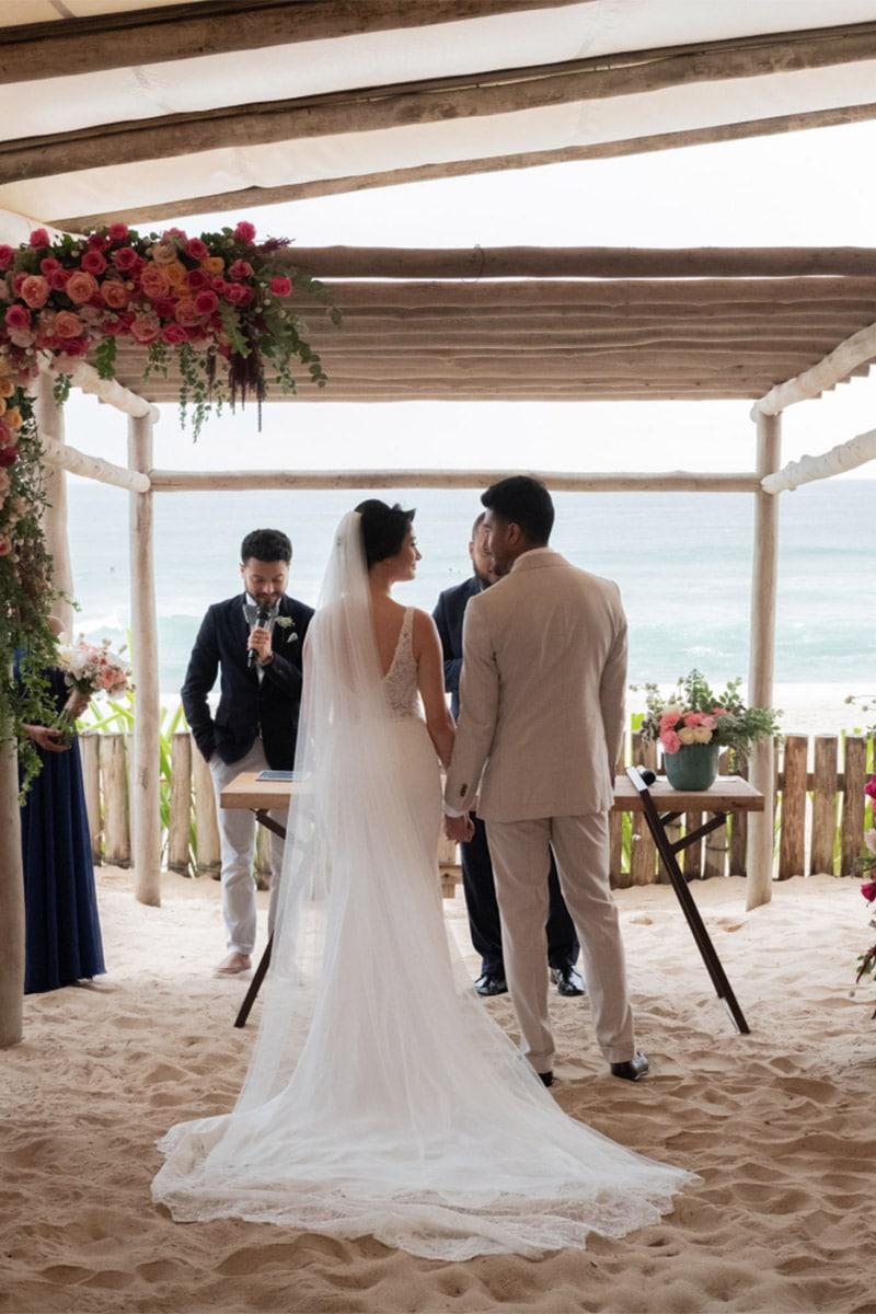 Trouwceremonie op strand bloemen