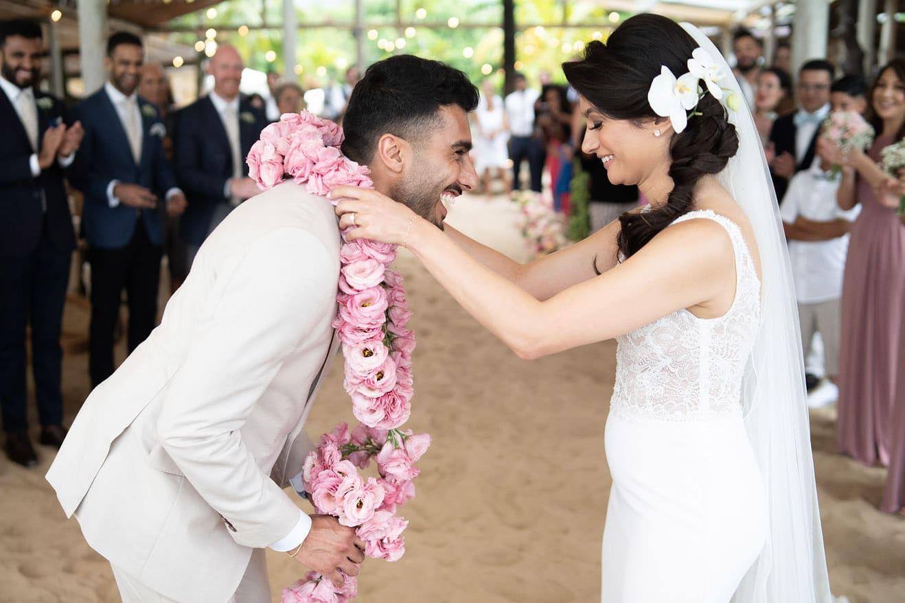 trouwceremonie met lichtroze bloemenkrans