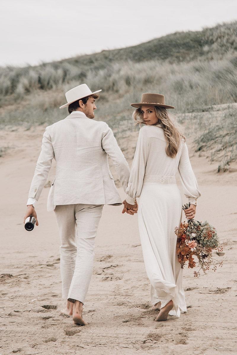 trouwoutfit met hoed op strand